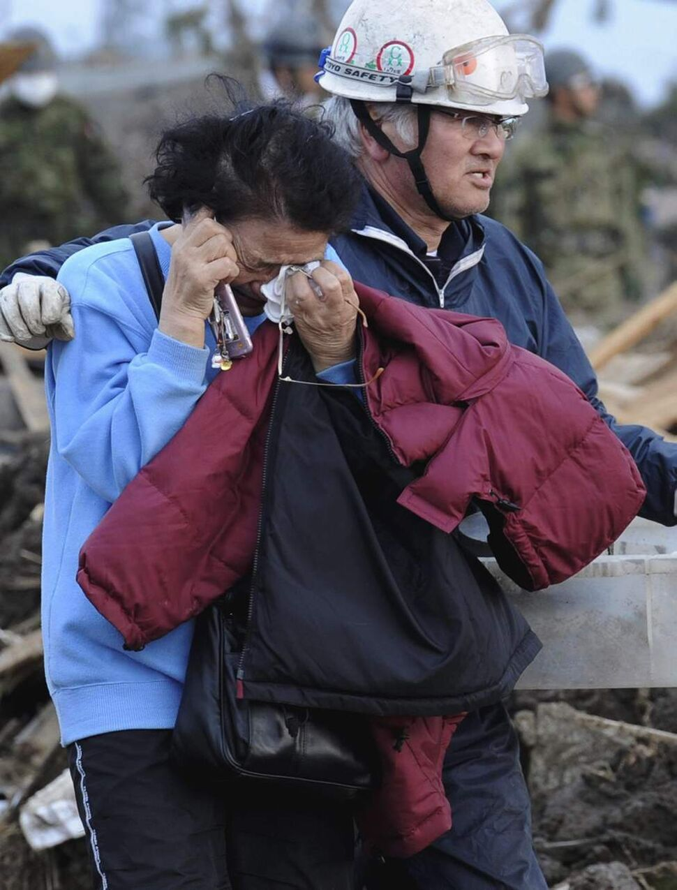 A man consoles a woman after she saw only the base of her house left in Noda village, northern Japan, Monday, March 14, 2011, three days after a powerful earthquake-triggered tsunami hit the country's east coast. (AP Photo/The Yomiuri Shimbun, Yoichi Hayashi)