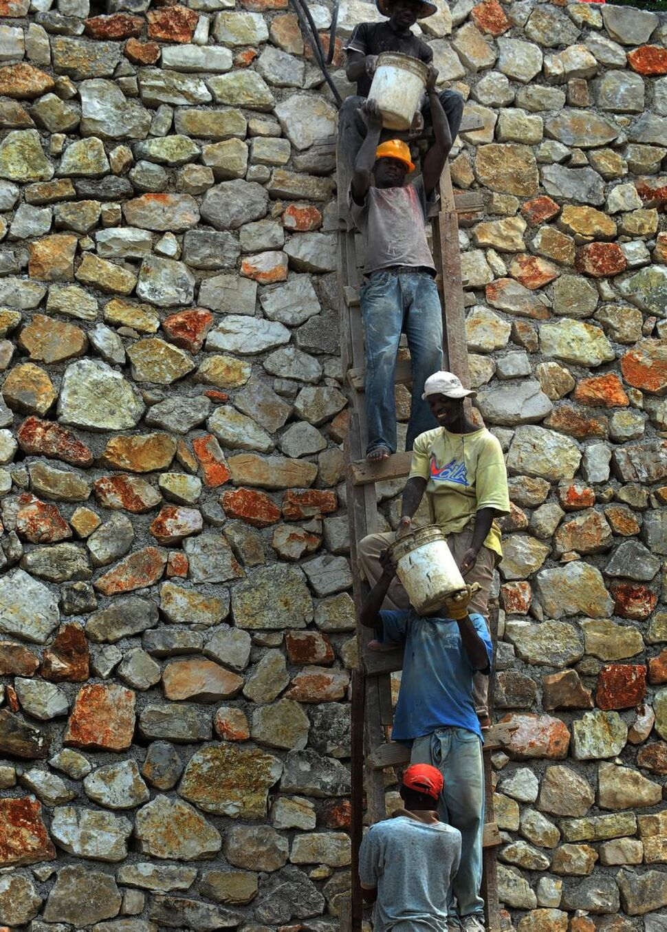 A group of Haitian workers share a ladder as they hoist sand buckets while constructing a retaining wall in Port-au-Prince, Haiti. (Ricky Carioti / Washington Post)