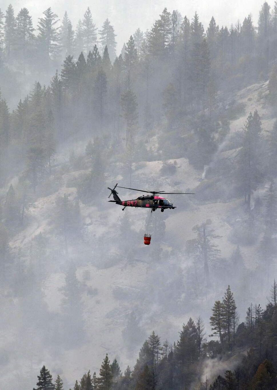 Fire crews prepare to drop water unto the Ponderosa Fire from a helicopter near Mineral, Calif.. The Ponderosa Fire was 57 per cent contained, with full containment expected early next week. The blaze threatened 900 other homes Thursday as it burned a new front to the south. More than 2,500 firefighters are battling the wildfire. (AP Photo/Marcio Jose Sanchez)