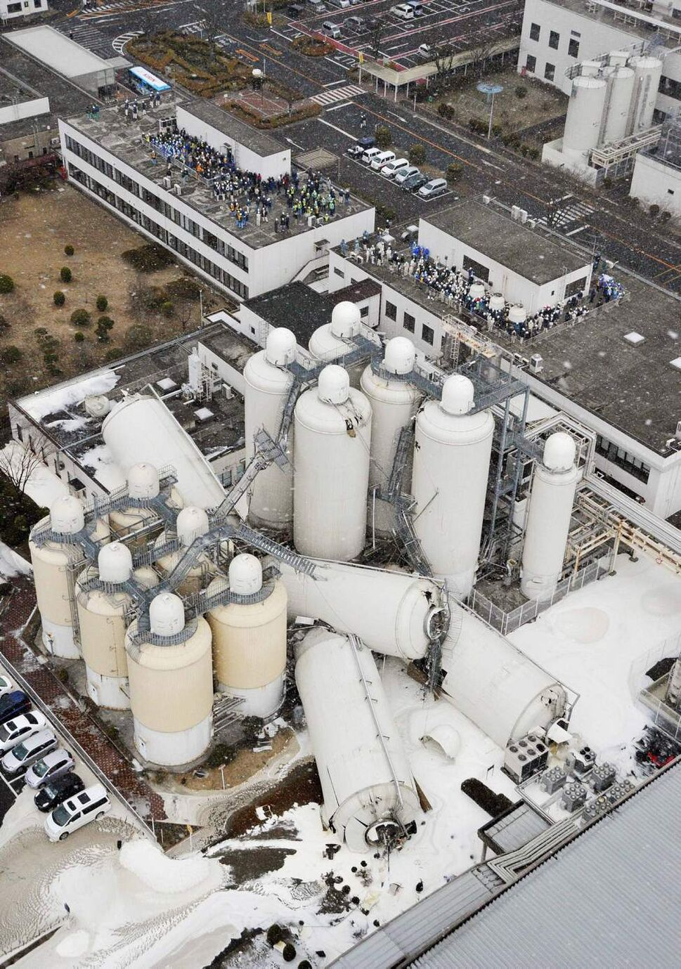 Parts of a beer factory's facilities are collapsed as the employees gather on the rooftops after a powerful earthquake in Sendai, Miyagi prefecture (state), Japan, Friday, March 11, 2011.  The largest earthquake in Japan's recorded history slammed the eastern coast Friday. (AP Photo/Kyodo News)