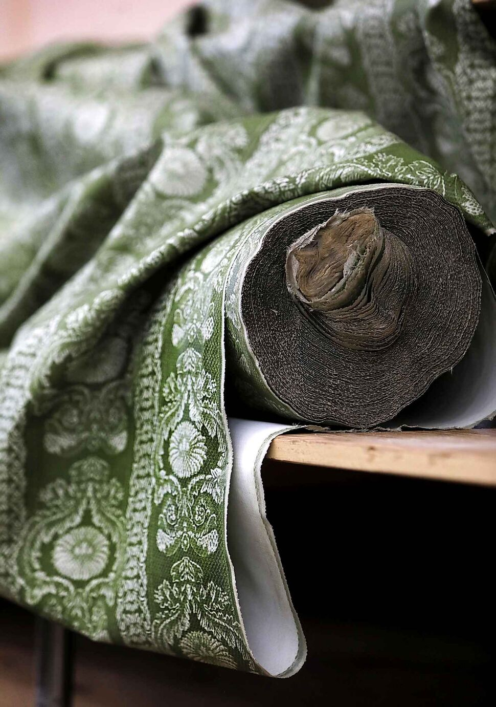 A bolt of olive green brocade fabric left behind on a shelf.   (Ruth Bonneville)