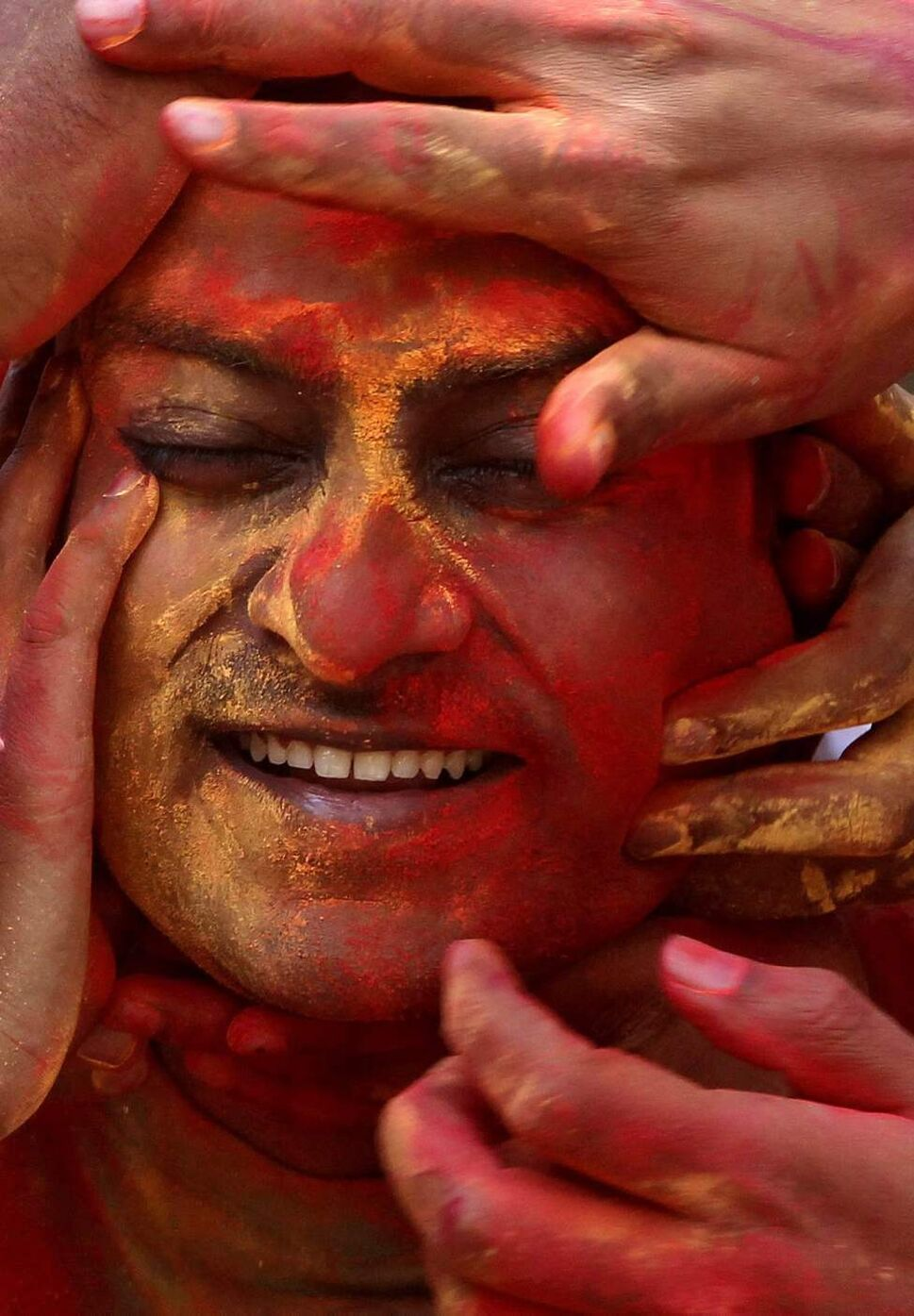 A man reacts as his face is smeared with colored powder by friends during Holi festivities in Mumbai, India, Thursday, March 8, 2012. Holi, the Hindu festival of colors, also heralds the coming of spring. (AP Photo/ Rajanish Kakade) (CP)