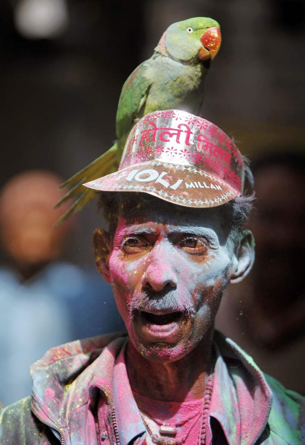 An Indian man with a colored face carries a parrot as he celebrates Holi in Jammu, India, Wednesday, March 7, 2012. Holi, the Hindu festival of colors will be celebrated across the country on March 8. (AP Photo/Channi Anand) (CP)