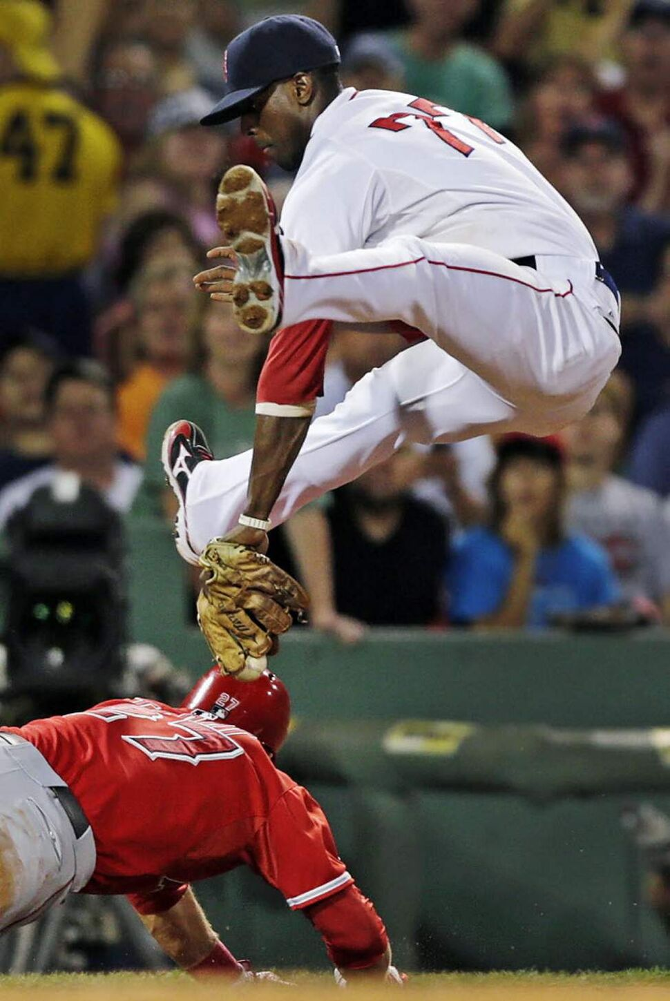 Boston Red Sox third baseman Pedro Ciriaco, top, drops his glove down between his legs as he tries unsuccessfully to catch Los Angeles Angels' Mike Trout diving back to third on a rundown in the third inning of a baseball game at Fenway Park in Boston. (AP Photo/Charles Krupa)