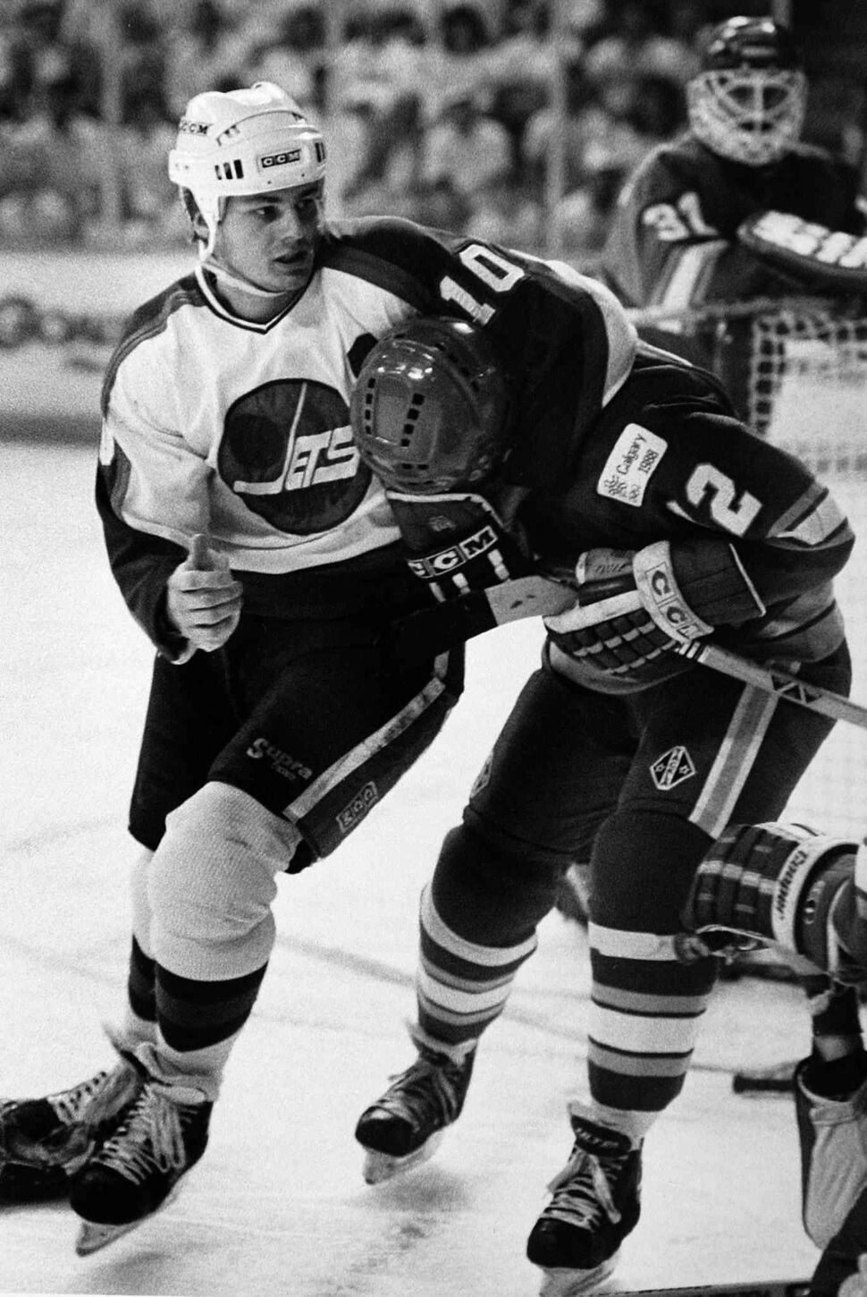 Hawerchuk grabs Calgary Flames forward Haken Loob with Flames goalie Rejean Lemelin looking on in a game on May 17, 1990. (Winnipeg Free Press files)