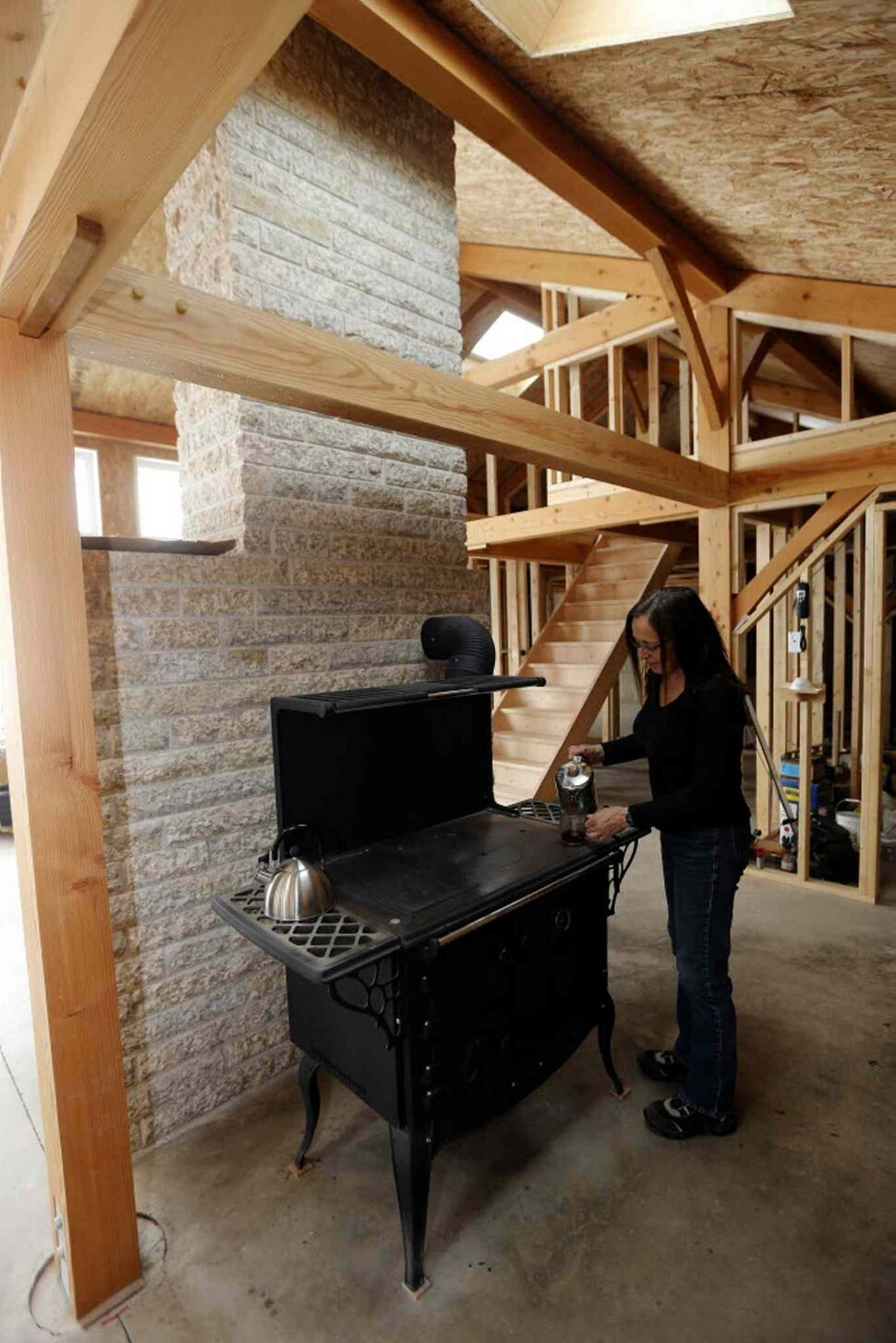 Bev Eert using a wood burning Waterford Stanley wood stove, but the house will have an electric stove when it is finished. (KEN GIGLIOTTI / WINNIPEG FREE PRESS)