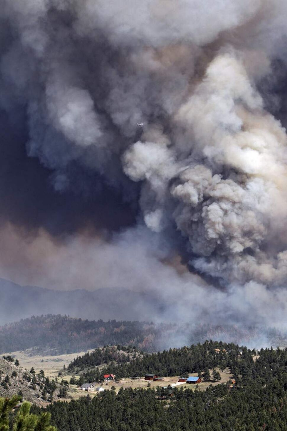 Fire burns behind homes north of Poudre Canyon in the Glacier View area near Livermore, Colo. The fire is burning on more than 68,000 acres west of Fort Collins and has destroyed at least 189 homes (AP Photo/Ed Andrieski)