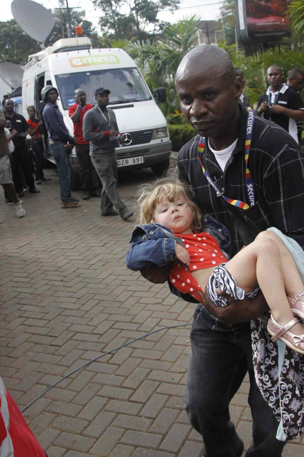 A security guard helps a child outside the Westgate Mall in Nairobi, Kenya, Saturday after gunmen threw grenades and opened fire during an attack that left multiple dead and dozens wounded. A witness to the attacks on the upscale shopping mall says that gunmen told Muslims to stand up and leave and that non-Muslims would be targeted. (Khalil Senosi / The Associated Press)