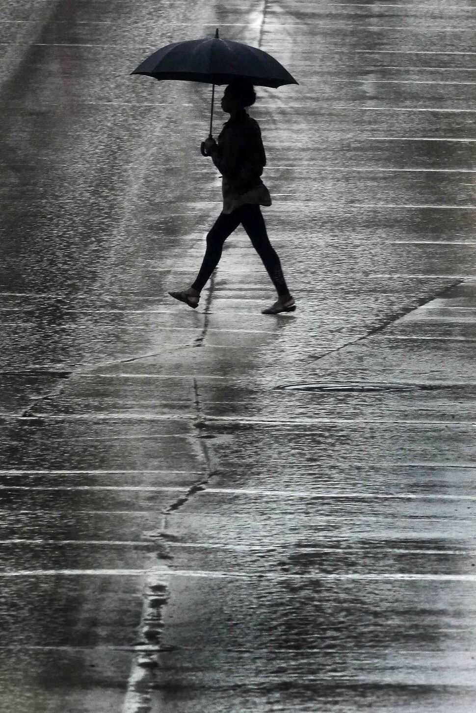 A pedestrian crosses Portage Avenue during a day of rainfall May 19, 2013. (John Woods / Winnipeg Free Press)