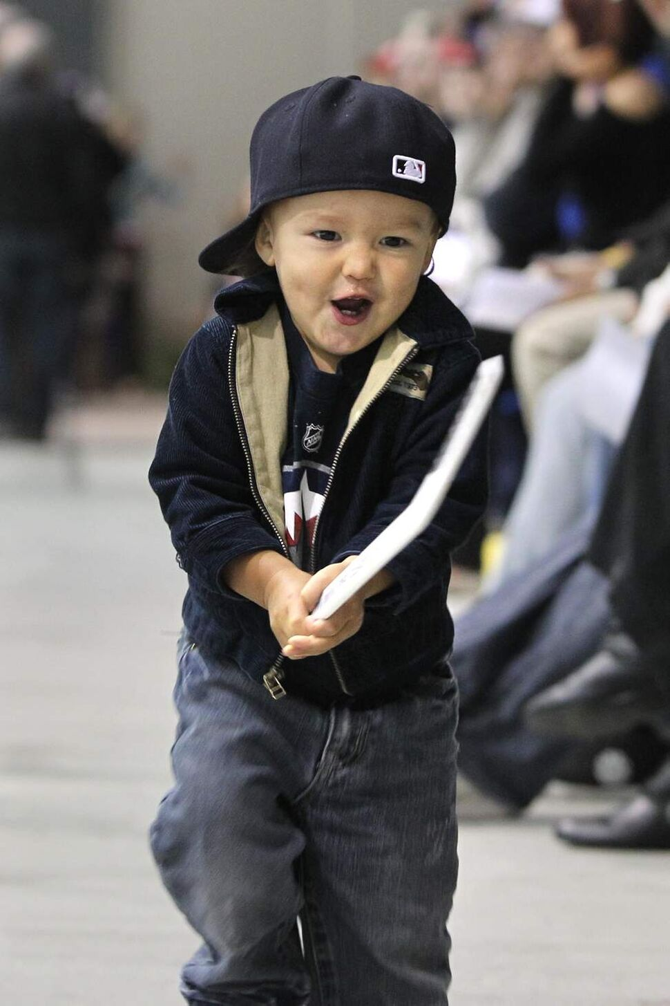 Seventeen-month-old Rocco Nakoyak cheers on the players on the ice during pracitce Saturday. (RUTH BONNEVILLE / WINNIPEG FREE PRESS)