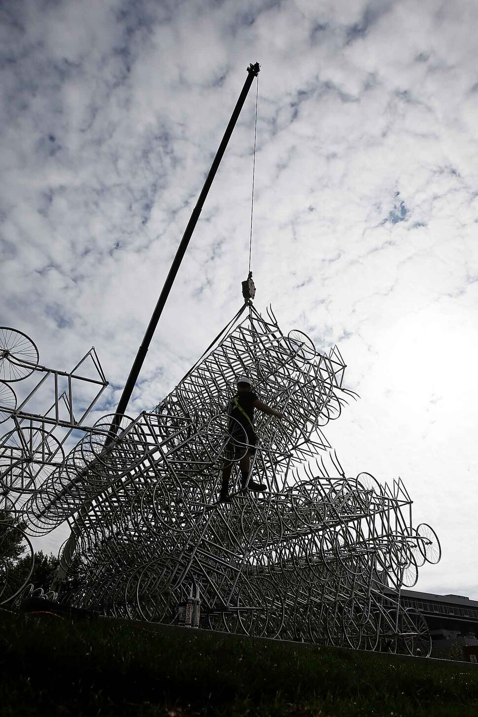 Matt Syles, art installation technician with MTEC, works on installing a bicycle sculpture by artist Ai Weiwei in Winnipeg Tuesday. (JOHN WOODS / WINNIPEG FREE PRESS)