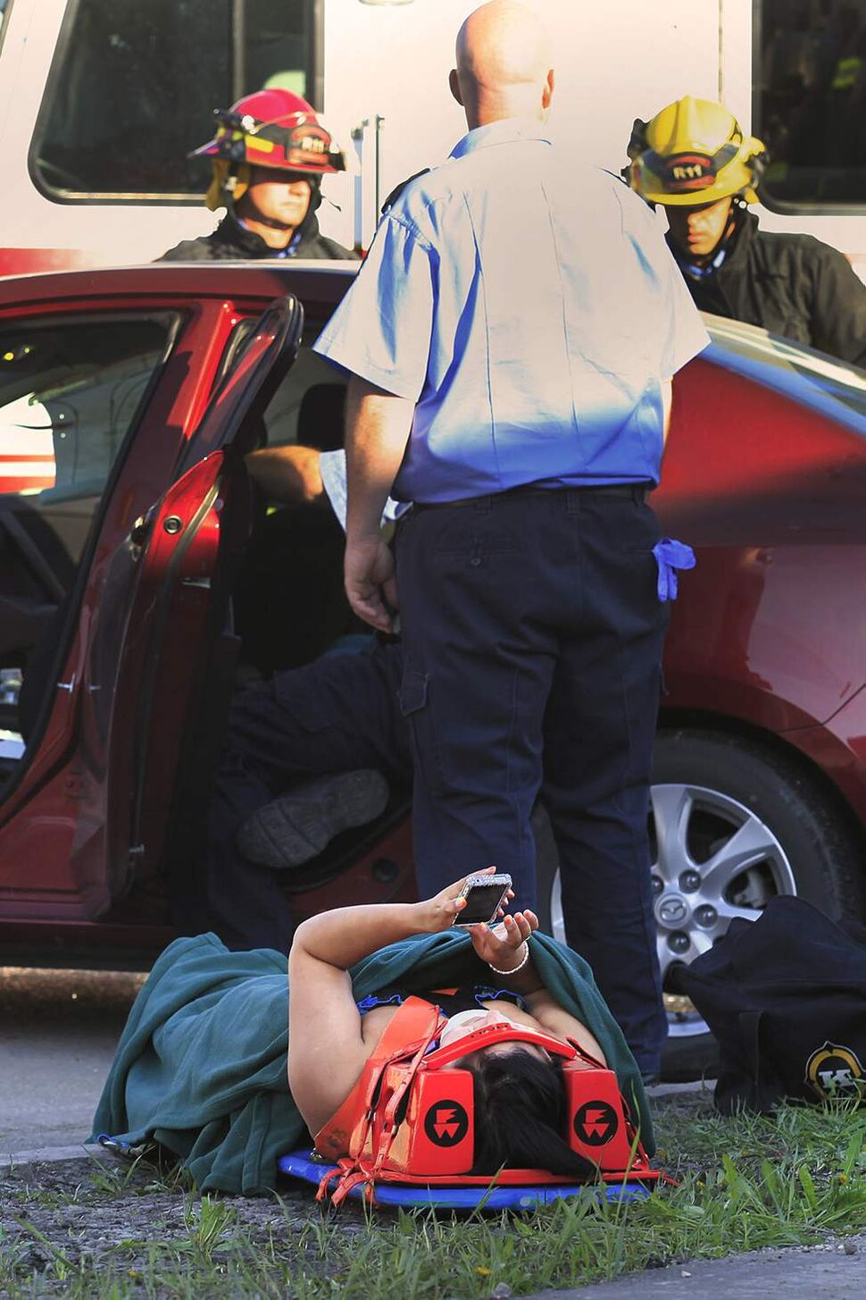 A woman texts as another passenger is extricated from her vehicle after a motor vehicle collision on Berry at Ness. May 26, 2011 (JOHN WOODS)