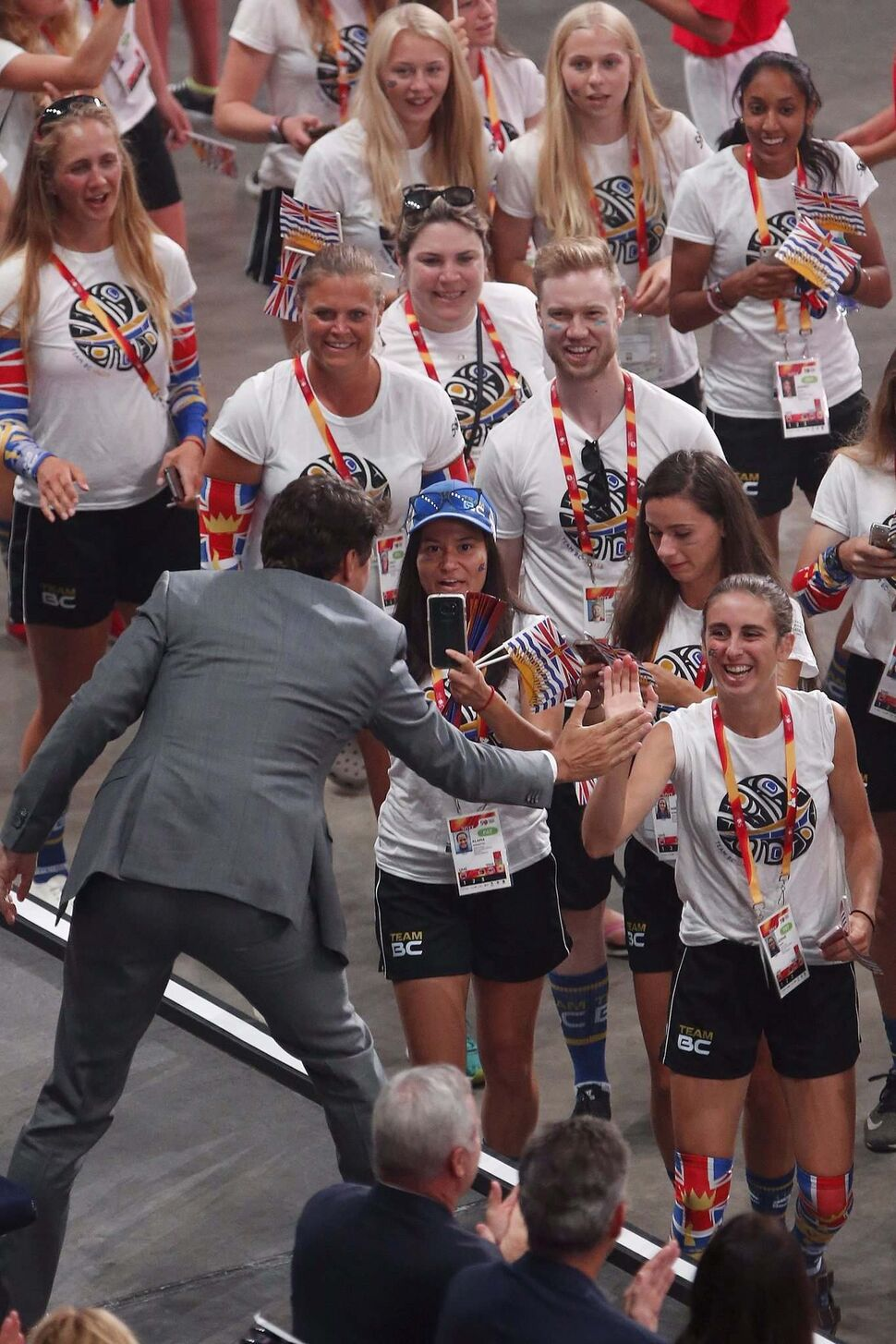 Prime Minister Justin Trudeau high-fives athletes. (JOHN WOODS / THE CANADIAN PRESS)