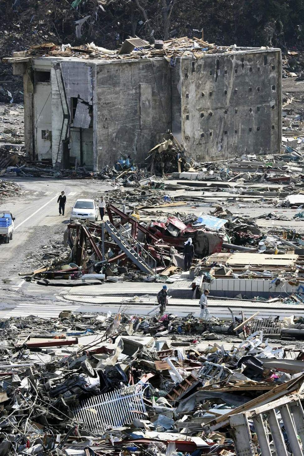 People walk through the rubble of destroyed buildings in Onagawa town, Miyagi Prefecture, northern Japan, Monday, March 14, 2011, three days after a powerful earthquake-triggered tsunami hit the country's east coast. (AP Photo/The Yomiuri Shimbun, Makoto Kondo)