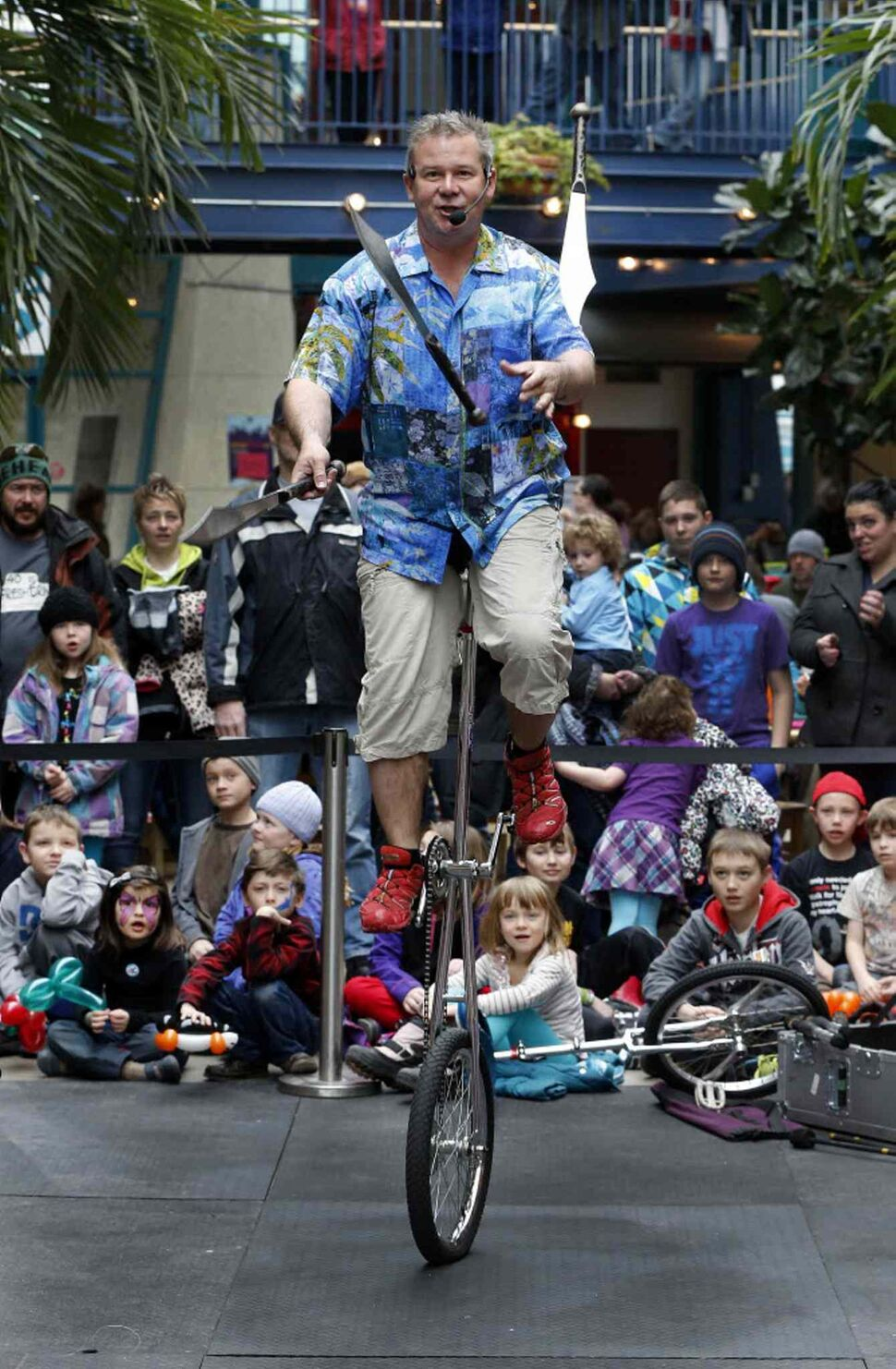 Battie juggles on his unicycle, capturing the attention of a crowd of kids at the Forks. (KEN GIGLIOTTI / WINNIPEG FREE PRESS)