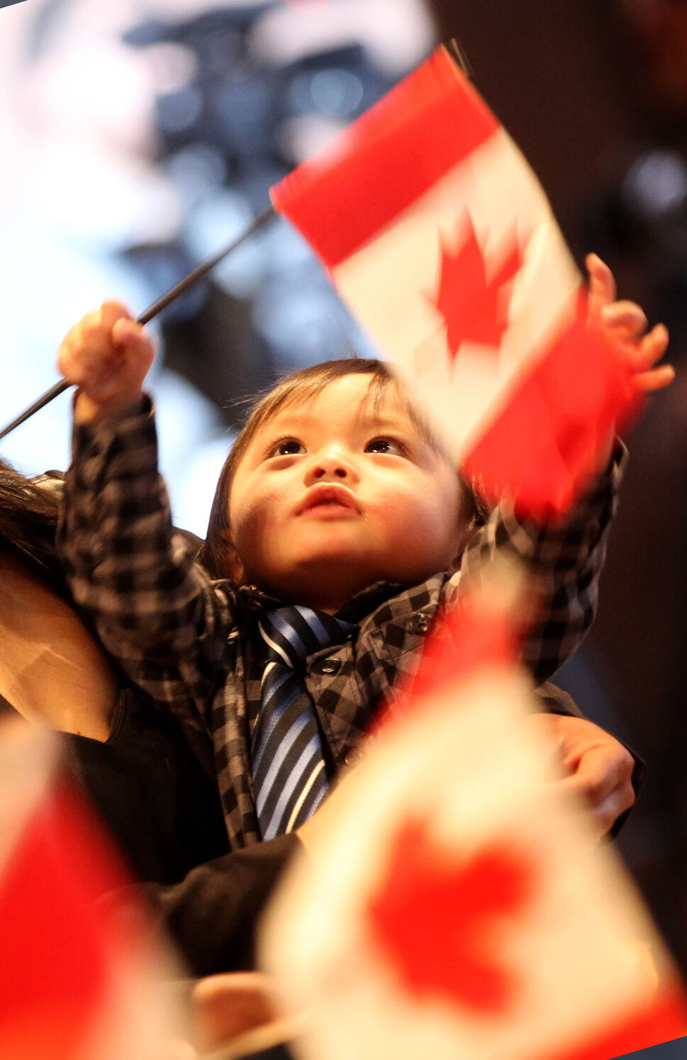 One-year-old Edrian Dulman looks up as he waves his Canadian Flag high while being held by his mom Catherine after he and his family received their Canadian Citizenship during a special ceremony at the CMHR. This was the first of many citizenship ceremonies to be held at the museum. 