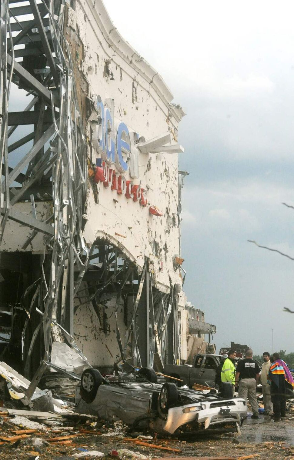 Emergency personnel assess the damage of the remains of the Academy Sports building at 17th St. and Range Line Road in Joplin, Mo. following the tornado that struck the city on Sunday evening. (Roger Nomer / The Associated Press)