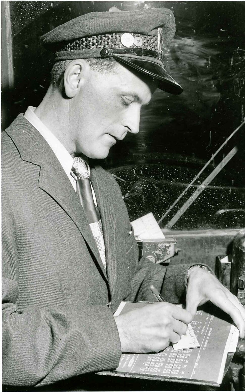 WINNIPEG FREE PRESS FILES A streetcar conductor autographs transfers during last trip of streetcar he was operating on Sept. 21, 1955.