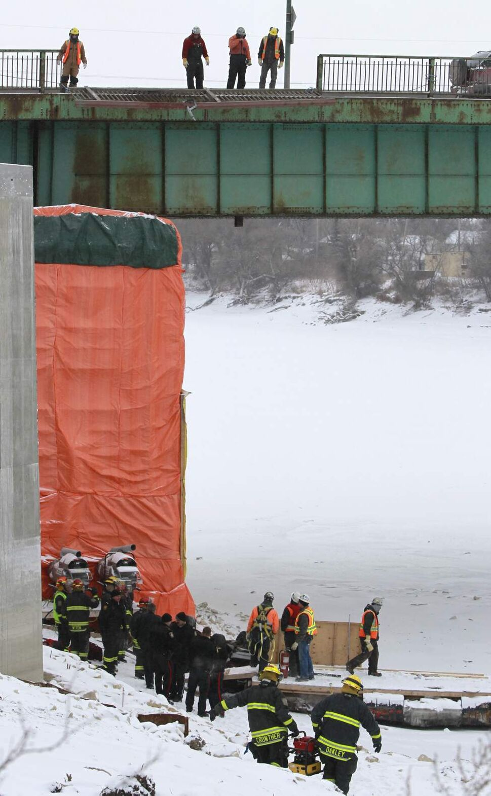Emergency crews and construction workers evaluate the scene where a vehicle crashed through a railing on the Disraeli Bridge near Midwinter Ave. and fell on the shore of the Red River. Kaitlyn Jenna Lee Fraser, 19, died in the crash. January 18, 2012      (WAYNE GLOWACKI/WINNIPEG FREE PRESS)