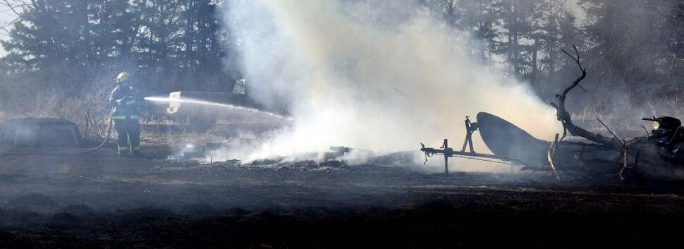 A Stonewall firefighter douses what is left of a storage shed on a rural property north of Stonewall Tuesday afternoon. An out-of-control grass fire destroyed the old barn and its contents and nearly consumed a nearby home. April 3, 2012  (Phil Hossack / Winnipeg Free Press)