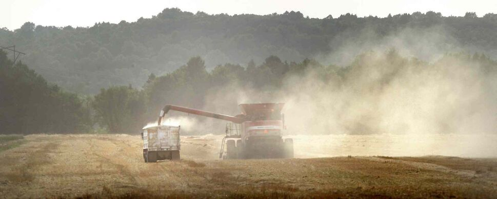 Dust frames a combine against the Manitoba Escarpment near Roseisle as it dumps grain from its hopper into a waiting grain truck. (Phil Hossack / Winnipeg Free Press)