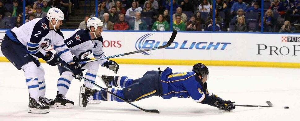 Blues left-winger Alexander Steen is knocked down from behind by Jets defenceman Mark Stuart (5) as he rushes the net in first-period action. (CHRIS LEE / ST LOUIS DISPATCH/AP)