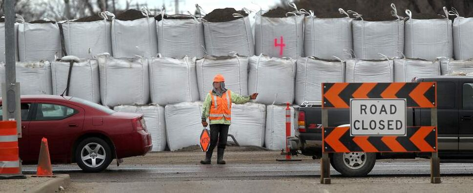 "A flag woman directs traffic past Giant ""superbags"" keeping the swollen Assiniboine River at bay in Brandon's Assiniboine Valley at 18th Street and Kirkaldy Drive. May 12, 2011. (Phil Hossack / Winnipeg Free Press)"