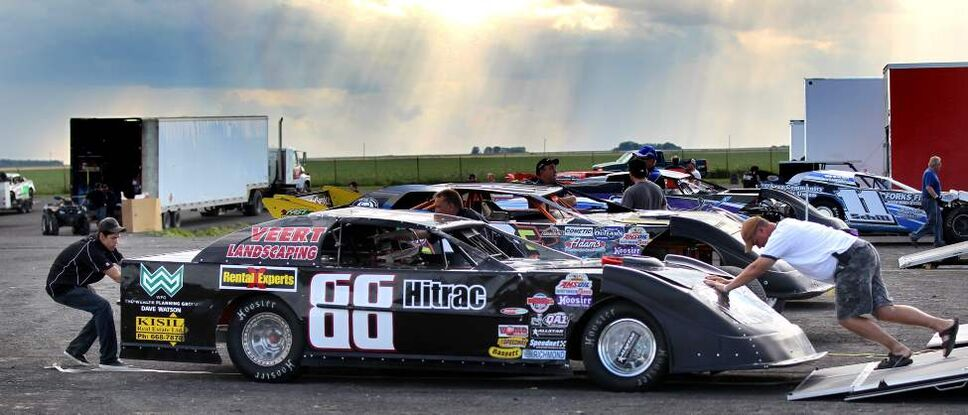 Pit crews and drivers push and pull cars out of their trailers for race night at Red River Co-op Speedway.