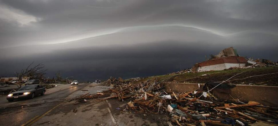 A shelf cloud containing a thunderstorm approaches a tornado-ravaged neighborhood in Joplin, Mo., Monday, May 23, 2011. A large tornado moved through much of the city Sunday, damaging a hospital, hundreds of homes and businesses and killing at least 89 people. (AP Photo/Charlie Riedel) (CP)