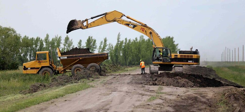 Construction crews work to bulk up the east side of the Portage Diversion near Highway 1. They are removing dirt from along the road and dumping it on the bank.  (TREVOR HAGAN/WINNIPEG FREE PRESS)