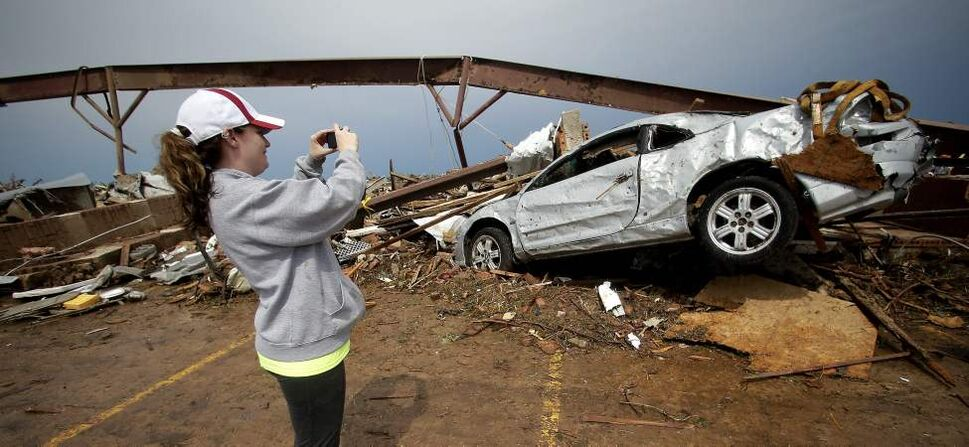 Heather Walker takes a photo of her tornado-ravaged car Tuesday outside the daycare where she works in Moore, Okla. Seven adults and 13 children  survived the tornado by huddling in the daycare's bathroom.  (Charlie Riedel / The Associated Press)