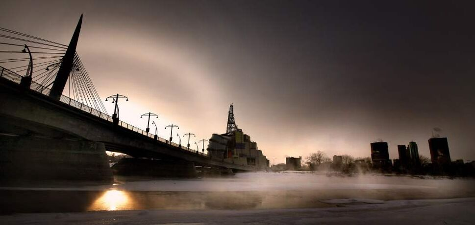 A crisp winter sun and its dog set behind the Esplanade Riel as a cold mist rises over the open Red River.  January 17, 2012 (Phil Hossack / Winnipeg Free Press)