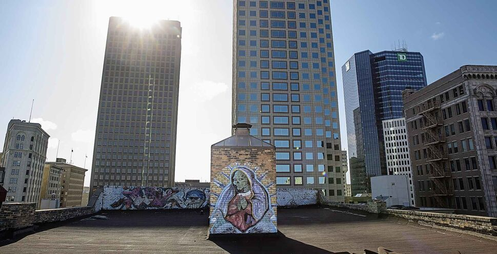 One of the murals sitting on the rooftop of the Gregg Building, being dwarfed by some of the taller downtown buildings.