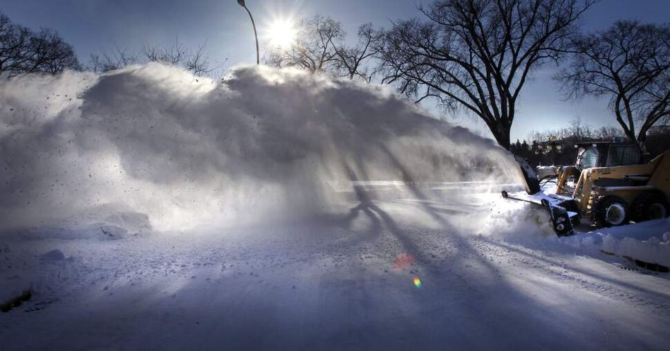 Snow is blown off a sidewalk on Assiniboine Avenue in front of a brilliant blue sky backdrop Monday.  (WAYNE GLOWACKI/WINNIPEG FREE PRESS)