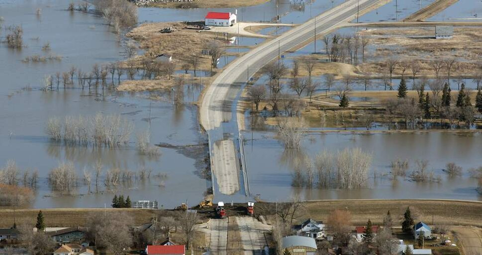 Highway 75, the main highway from Winnipeg,  is closed because of the flooding Morris River and Red River. Crews work, lower-center, to close ring dikes around the town of Morris to protect them from the rising water.  JOE BRYKSA/WINNIPEG FREE PRESS