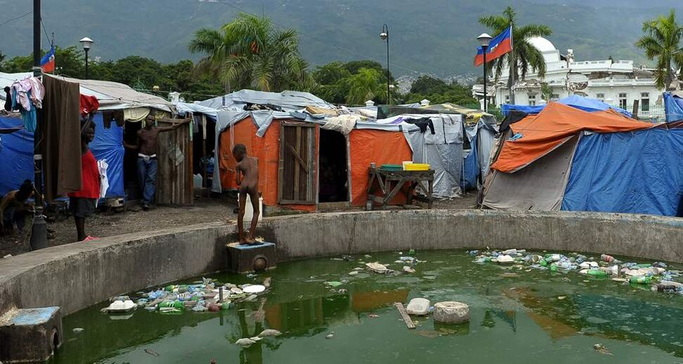 A young boy bathes in a fountain at a displacement camp outside the presidential palace on August 14, 2010 in Port-au-Prince, Haiti. (Ricky Carioti / Washington Post)