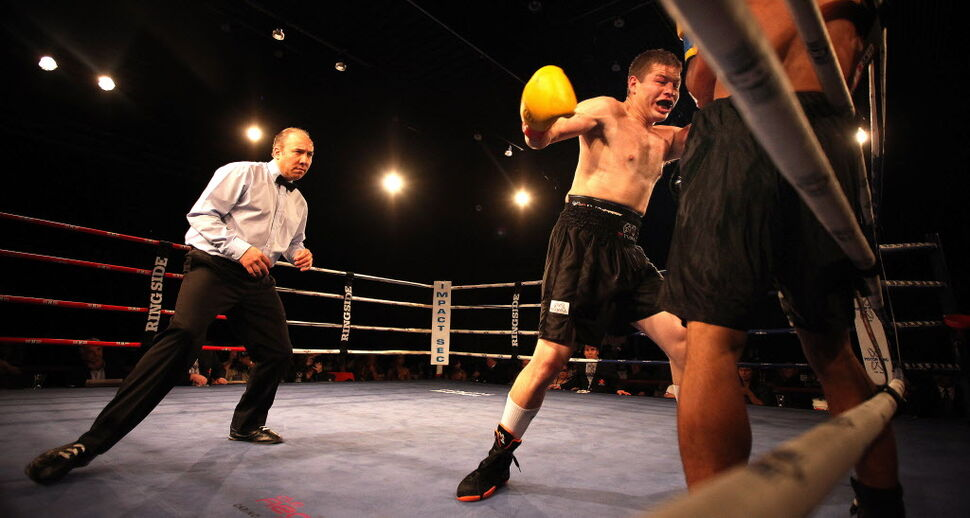 Winnipeger Kelly Page, on his way to a professional debut win, delivers a blow to Dia Grant's midsection. (Phil Hossack / Winnipeg Free Press)