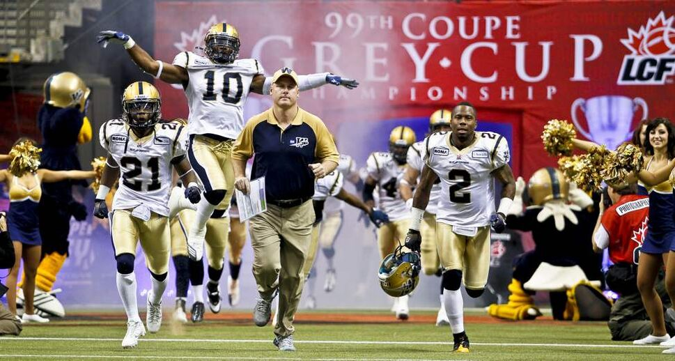 Winnipeg Blue Bombers head coach Paul LaPolice runs out with his team at the start of the 2011 Grey Cup final between the Winnipeg Blue Bombers and the B.C. Lions.