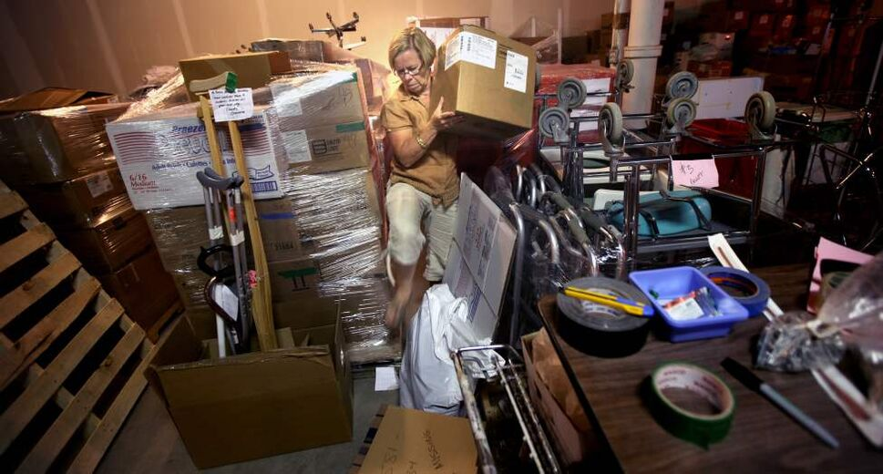 OR nurse Karen Watchorn shifts supplies in a St James warehouse readying the inventory for shipment to Nicaraugua. (Phil Hossack / Winnipeg Free Press)