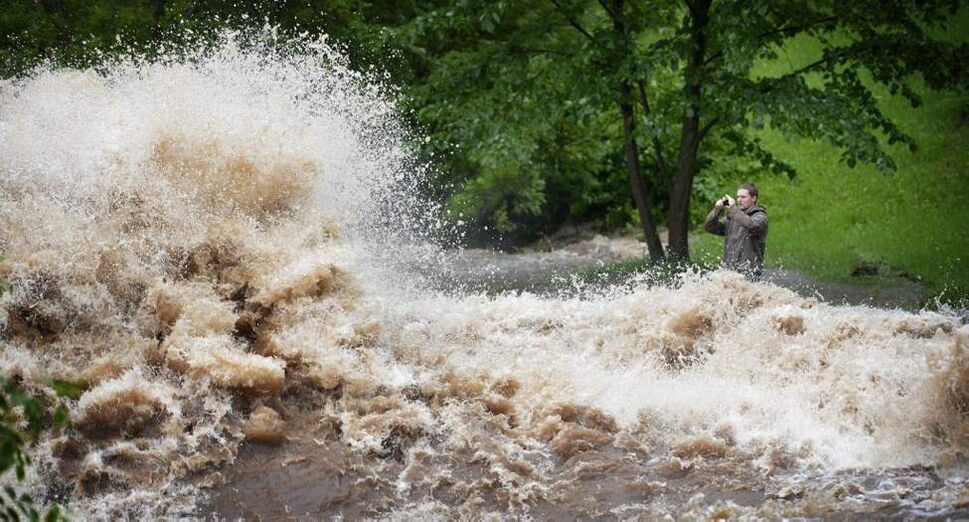 A man gets dangerously close to the raging Miller Creek as it flows through Lincoln Park in West Duluth, Minn. (AP Photo/The Star Tribune, Brian Peterson)
