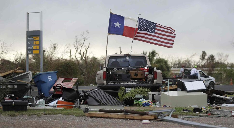 The Texas state flag and American flag wave in the wind over an area of debris left behind in the wake of Hurricane Harvey, Sunday, Aug. 27, 2017, in Rockport, Texas. (AP Photo/Eric Gay)