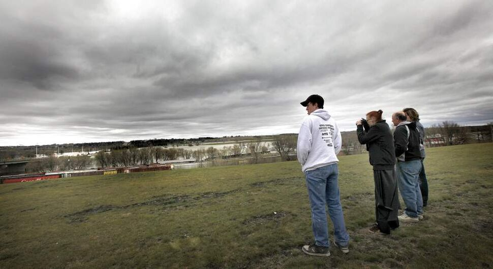 Left to right, Fritz, Kathy and Craig Horback of Minnedosa and of Melinda Day Virden Manitoba, survey the swollen Assinaboine RIver from a high park near First Street in Brandon.  May 12, 2011. (Phil Hossack / Winnipeg Free Press)
