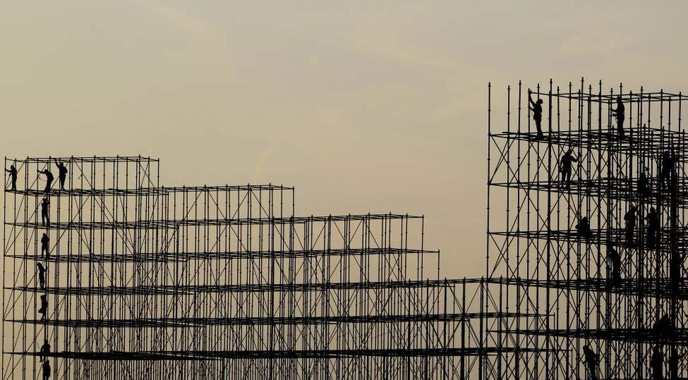 Laborer workers set up scaffoldings to prepare for the World Parachuting Championship in Dubai, United Arab Emirates, Tuesday, Oct. 23, 2012. (AP Photo/Kamran Jebreili)