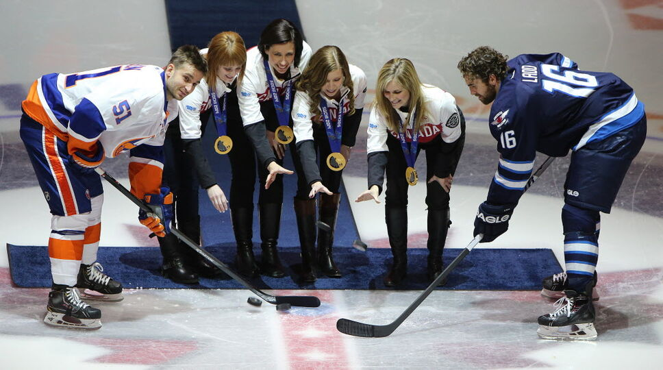 Olympic gold medal-winning skip Jennifer Jones (second right) and her curling team (from second left) Dawn McEwen, Jill Officer and Kaitlyn Lawes take part in the ceremonial puck-drop before the Winnipeg Jets took on the New York Islanders on Tuesday.  (Jason Halstead / Winnipeg Free Press)