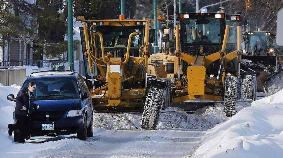 Hurry, hurry. The owner of a car parked on Burrows Street gets to her car just in time as a line of graders and loaders arrive to clean the latest snowfall. January 24, 2014 (KEN GIGLIOTTI / WINNIPEG FREE PRESS)