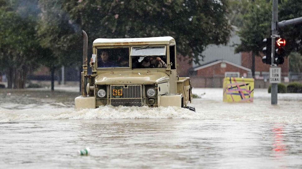A truck pushes through floodwaters on Sunday, Aug. 27, 2017, in Houston, Texas.  (David J. Phillip / The Associated Press)