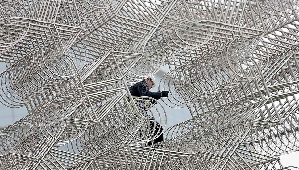 Forever Bicycles overseer Dan Page clambers over the  sculpture Thursday. (PHIL HOSSACK / WINNIPEG FREE PRESS)