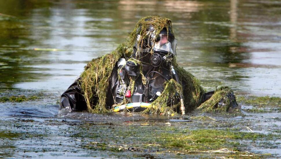 A member of the WPS Underwater Search and Recovery Unit comes out of the water covered in reeds while searching for a man that is believed to have drown on July 16 in the pond at Albina Park. July 17, 2012 (Ruth Bonneville Winnipeg Free Press)