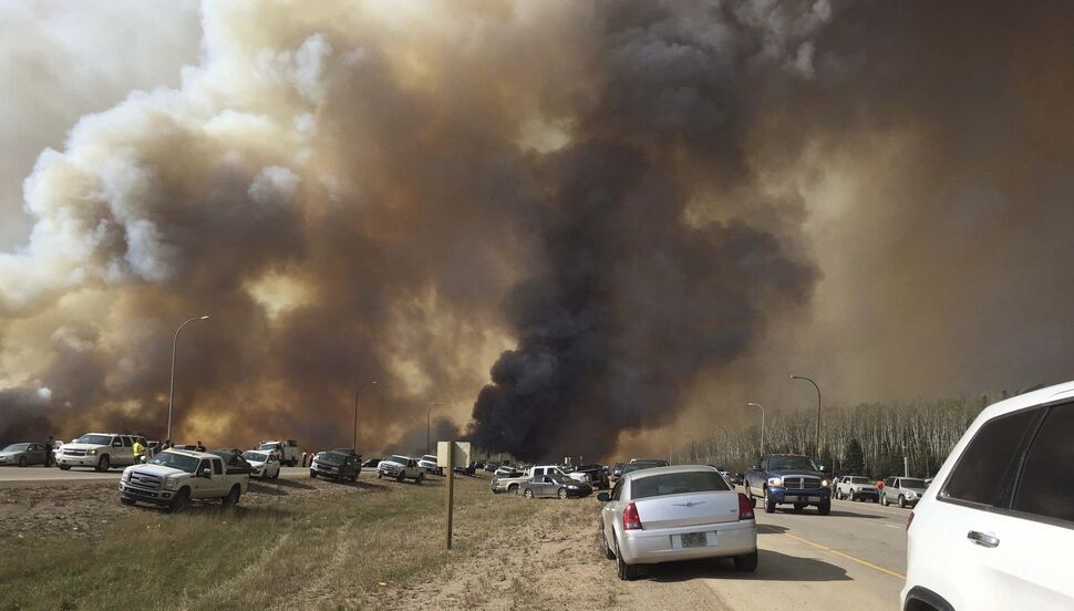 Brian Langton / The Canadian Press</p><p>Abandoned vehicles litter Highway 63, south of Fort McMurray, Alta., as residents flee the wildfire engulfing the oilsands city.</p>