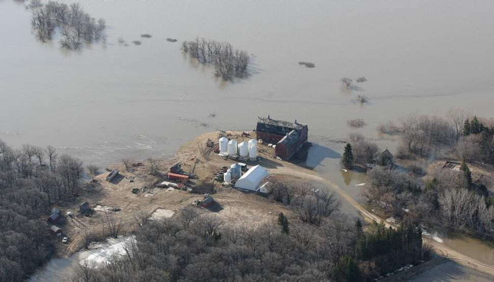 A farm is surrounded by the flooding Red River near the town of St Jean Baptiste Wednesday. JOE BRYKSA/WINNIPEG FREE PRESS